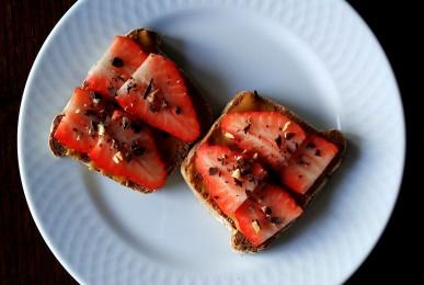 Pan de centeno integral con crema de cacahuete, fresas y chocolate negro rallado