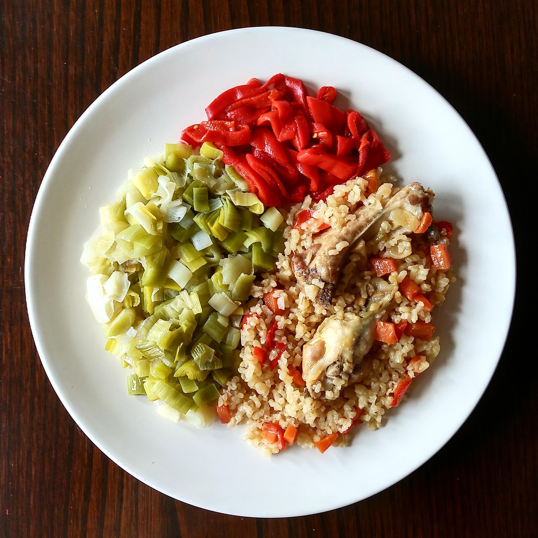 Pollo guisado con arroz integral, puerro y pimientos asados
