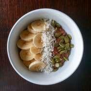 Porridge de avena y cacao con plátano, coco rallado y pipas de calabaza