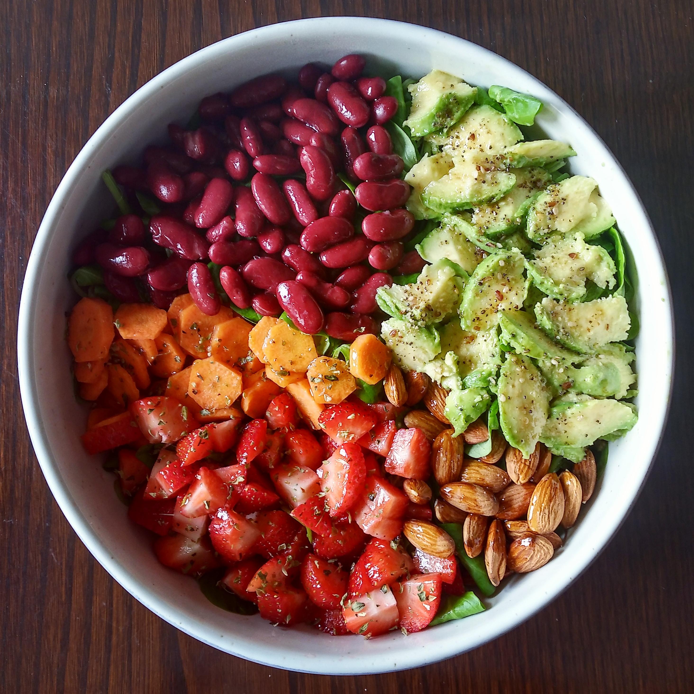 Bol de brotes, azukis, aguacate, almendras, fresas y zanahoria