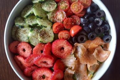 Bol de brotes, salmón ahumado, fresas, pepino, tomatitos cherry y aceitunas