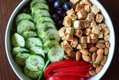 Bol de canónigos y rúcula con pepino, aceitunas negras, tofu aliñado con pimentón dulce, almendras y pimiento rojo