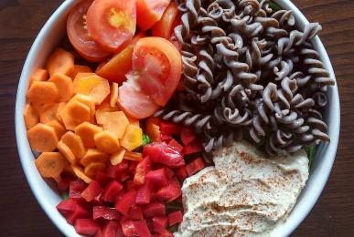 Bol de espinacas, pasta de lentejas, hummus, tomate, zanahoria y pimiento rojo