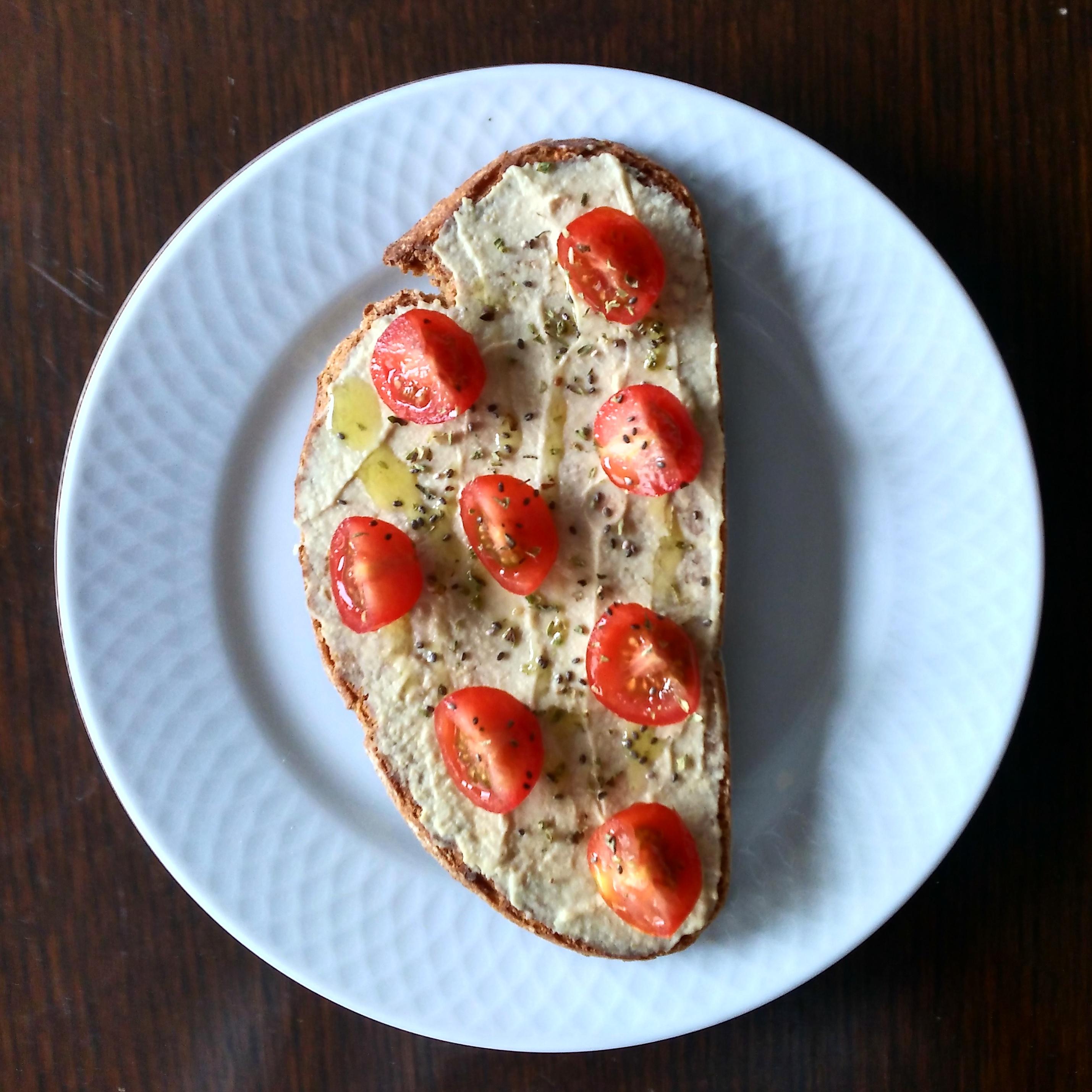 Tostada integral con hummus, tomatitos cherry y orégano