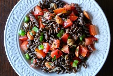 Ensalada de espirales de lenteja, tomate, pimiento verde, setas y almendras