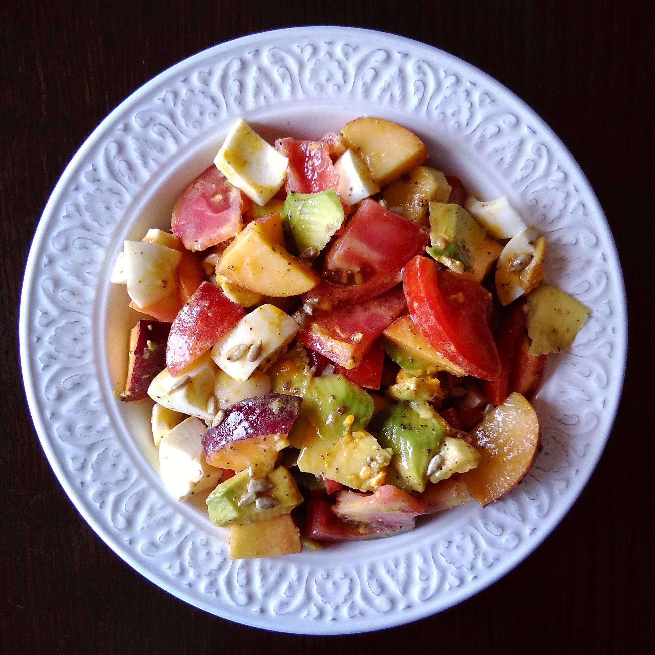 Ensalada de tomate, aguacate, melocotón, huevo cocido, pipas de girasol y semillas