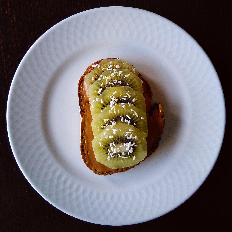 Tostada integral de crema de cacahuete, kiwi y coco rallado
