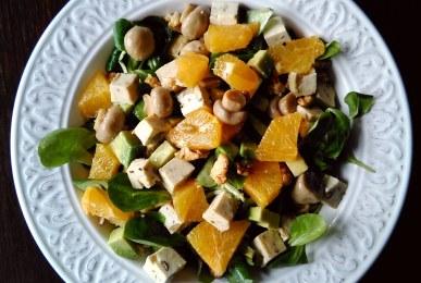 Ensalada de canónigos, aguacate, champiñones, naranja, nueces y tofu con aceitunas